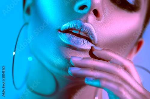 Poster Beauty High fashion model woman in colorful bright neon lights posing in studio. Beautiful sexy girl, trendy glowing makeup, metallic silver lips