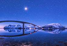 Bridge And Purple Starry Sky With Beautiful Reflection In Water. Night Landscape With Bridge, Snowy Mountains, Sky With Full Moon And Bright Stars Reflected In Sea. Winter In Lofoten Islands, Norway