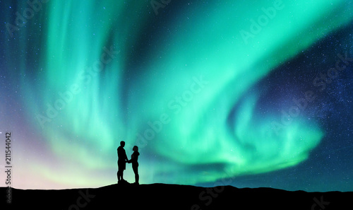Photo  Northern lights and hugging couple on the hill