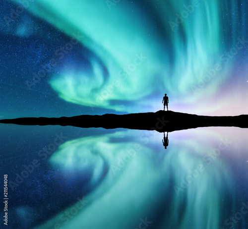 Wall Murals Green coral Northern lights and silhouette of standing man in the hill in Norway. Aurora borealis and man. Stars and green polar lights. Night landscape with aurora, lake, sky reflection in water. Travel. Concept