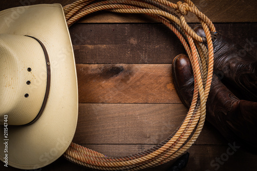 Fényképezés A cowboy hat, lariat rope and boots on a wooden plank background
