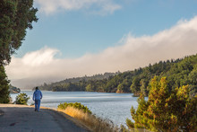 Man Walking On A Path Adjacent To Crystal Springs Reservoir As The Fog Lifts Over The Foot Hills