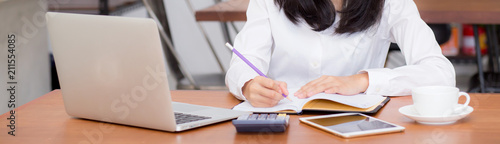 Foto  Closeup banner asian woman writing on notebook on table with laptop, girl work at coffee shop, freelance business concept