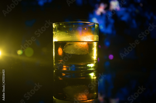 Tuinposter Alcohol selective focus pure whisky with ice cube inside whisky glass on dark foggy background alcohol drink concept.