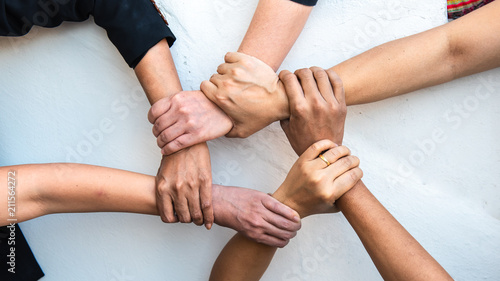 Fotografía  Group of young business people united, joining , combine hands together expressing positive, unity, volunteer , teamwork concepts