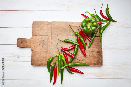 Photo  Red, green chili and paprika pepper presented on an old wooden board on a white wooden background