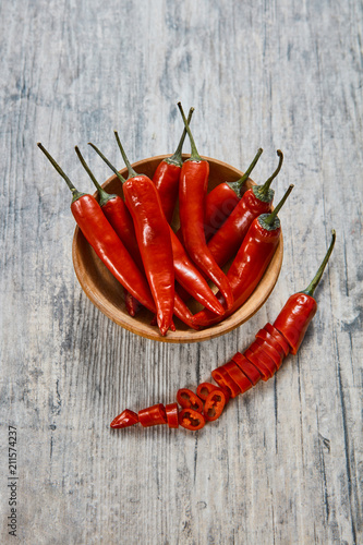 Photo  Red chili pepper in a brown clay plate on an old wooden table