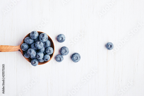 Tableau sur Toile Ripe bluberries in wooden spoon on white wooden table. Top view.