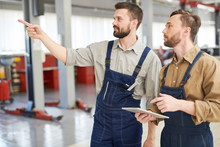 Waist Up Portrait Of Two Modern Bearded Mechanics Walking Across Workshop And Pointing Away  While Working In Car Service And Repair Center, Copy Space