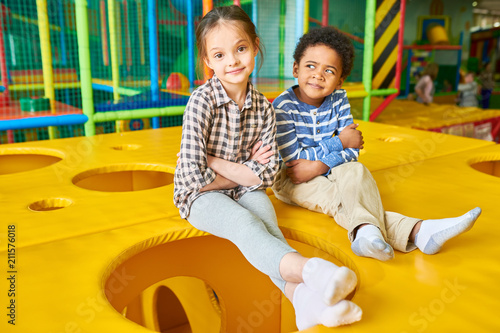 Full length portrait of cute girl and African-American boy posing sitting on top Wallpaper Mural