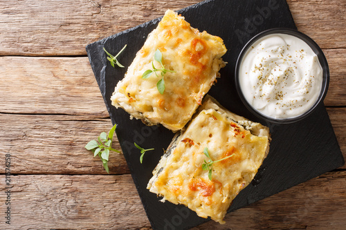 Italian layered lasagna with chicken breast, mushrooms, cheese, herbs and bechamel sauce close-up on a plate. horizontal top view