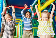 Waist Up Portrait Of Three Happy Kids Jumping Raising Hands While Having Fun In Play Area And Looking At Camera