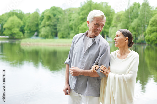 Leinwand Poster Happy senior couple walking along waterside in public park among green trees
