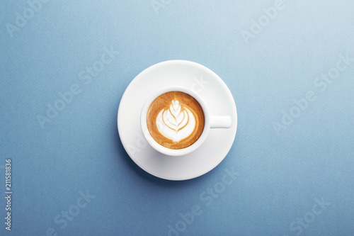 Foto A cup of cappuccino with beautiful latte art on blue background