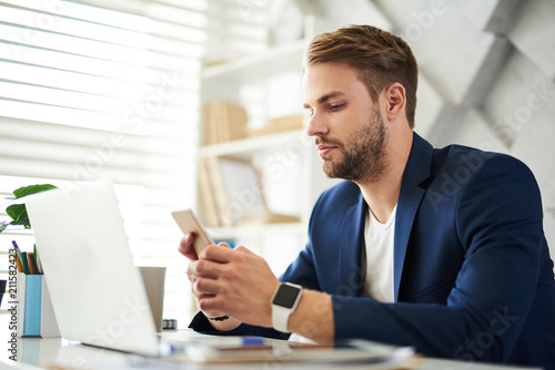 Fotografía  Side view profile of serene man sitting at desktop in cabinet with phone in hands