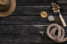 Tourist Hat, Shovel Full Of Gold Ore, Compass, Rope And Magnifying Glass On Aged Wooden Table Background. Treasure Hunter Concept.