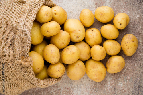 Papiers peints Echelle de hauteur Sack of fresh raw potatoes on wooden background, top view.