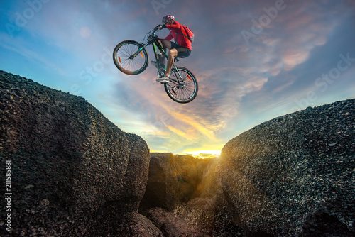 Professional rider is jumping on the bicycle, with background of sunset, racing Fototapeta