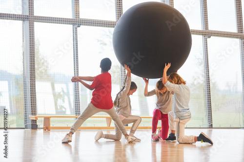 Obraz na plátně  Schüler heben in Teamwork einen riesigen Ball