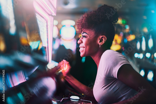 Fotografering happy woman gambling at casino playing slot machine