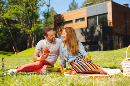 Fotobehang Ontspanning Good mood. Pleased bearded man holding watermelon and talking with his wife