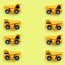 Many Small Yellow Toy Trucks On Texture Background Of Fashion Pastel Yellow Color Paper In Minimal Concept