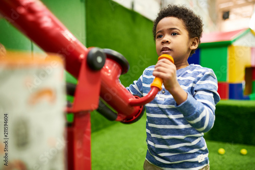 Obraz Colorful waist up portrait of cute African-American boy having fun playing in children center, copy space - fototapety do salonu