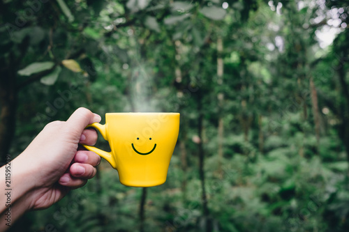 Hand holding hot yellow coffee cup with hand drawn smile face on cup at tropical nature forest,Leisure lifestyle.
