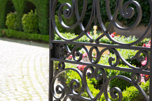 A Wrought Iron Gate Open To Th...