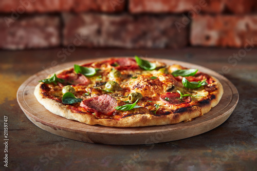 Thin crust pizza with ham, cheese and olive.  Freshly baked pizza (from wood-fired oven).