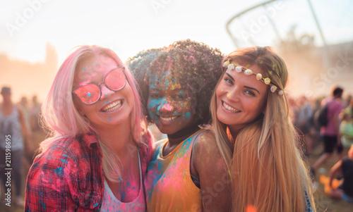 Multiethnic girls covered in colorful powder celebrating summer holi festival