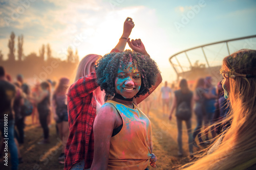 Obraz Multiethnic girls covered in colorful powder celebrating summer holi festival - fototapety do salonu