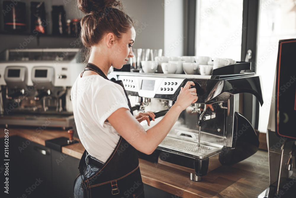 Fototapeta Young woman barista preparing coffee using machine in the cafe