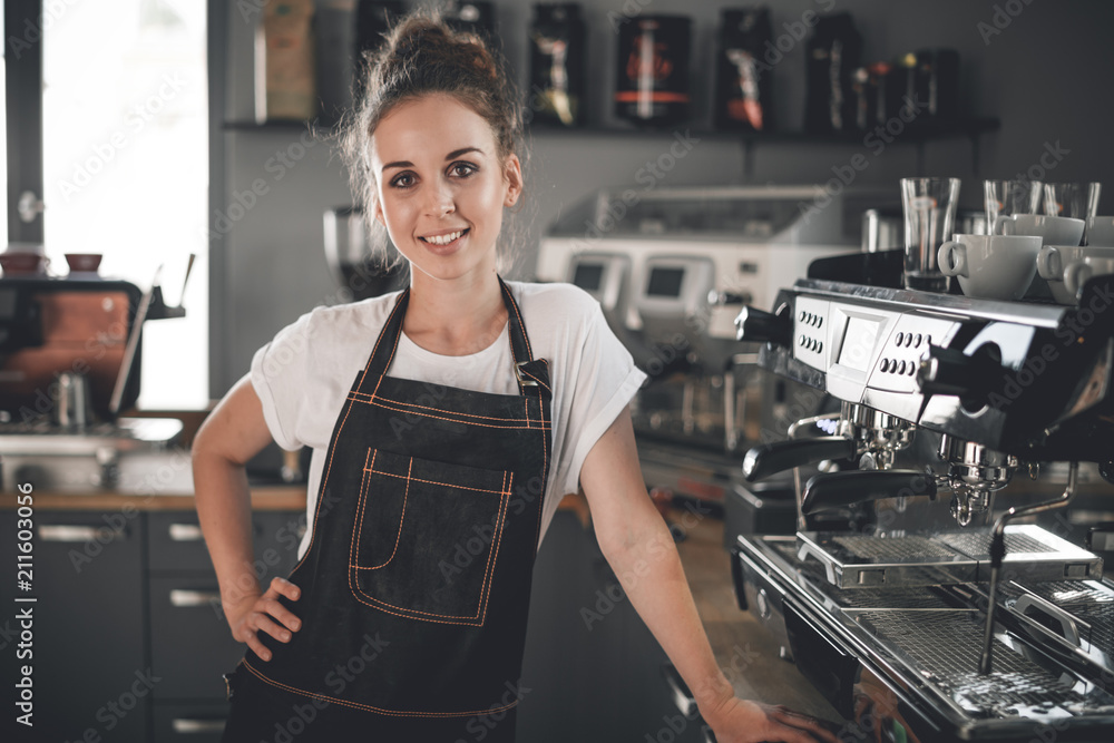 Fototapeta Young smiling cafe business owner standing at bar in coffee shop