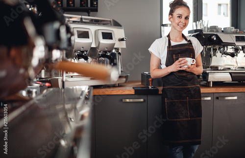 Young smiling cafe business owner standing at bar in coffee shop