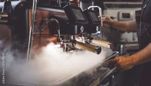 Coffee machine in steam, barista preparing coffee at cafe