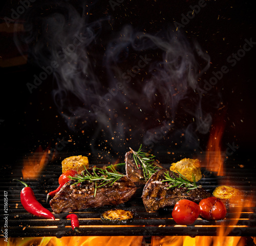 Aluminium Prints Grill / Barbecue Beef steaks on the grill with flames