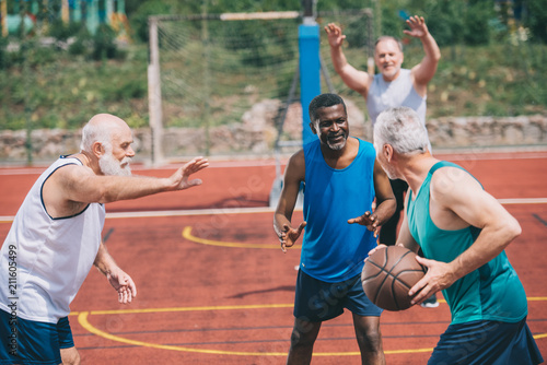 interracial elderly sportsmen playing basketball together on playground Poster Mural XXL
