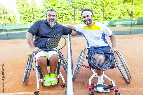Fotografie, Obraz  pair of disabled tennis players hugging each other under the net