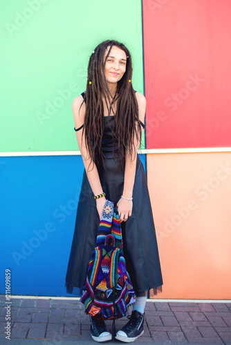 Photo  Beautiful slim girl with dreadlocks, a rastaman, in a black dress and sneakers, stands against the background of a multi-colored wall, holding a cloth backpack in her hands