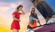 road trip, transport, travel and people concept - young women with open hood of broken car over evening sky background
