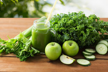 Healthy Eating, Food, Dieting And Vegetarian Concept - Glass Mug Or Mason Jar With Green Juice, Fruits And Vegetables On Wooden Table Over Natural Background
