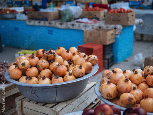 big bowl with pomegranates in street market