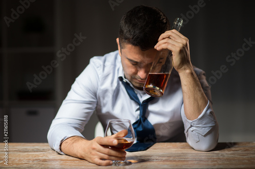 Poster de jardin Bar alcoholism, alcohol addiction and people concept - male alcoholic with bottle drinking brandy at table at night