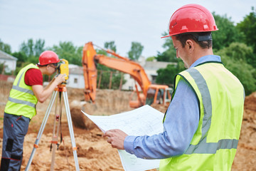 Fototapeta Construction workers on building area. Foreman with blueprint and surveyoor