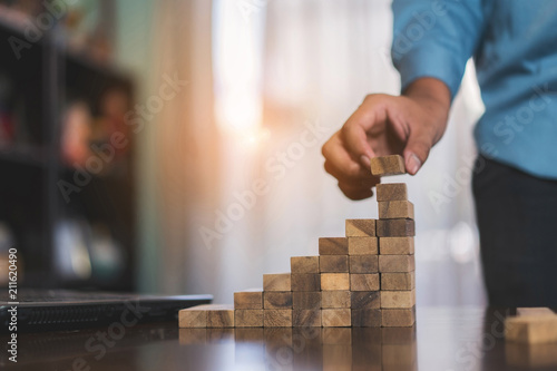Businessman planing and strategy putting wooden blocks risk or success project stack of danger tower hands playing challenge game building construction protect at office Canvas Print