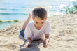 a six-year-old boy in a white t-shirt playing with sand on the river Bank on a Sunny morning