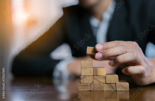 Businessman planing and strategy putting wooden blocks risk or success project hands control stack of danger tower challenge game building construction protect at office Wallpaper Mural