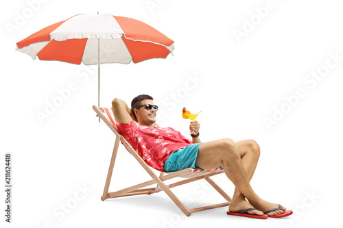 Canvas Print Tourist with a cocktail sitting in a deck chair with an umbrella