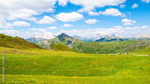 In de dag Pistache Landscape of Dolomites with green meadows, blue sky, white clouds and rocky mountains.
